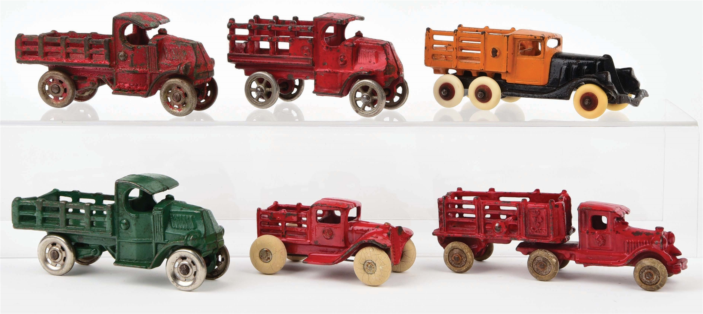 LOT OF 6: CAST-IRON AMERICAN MADE STAKE BACK TRUCKS.